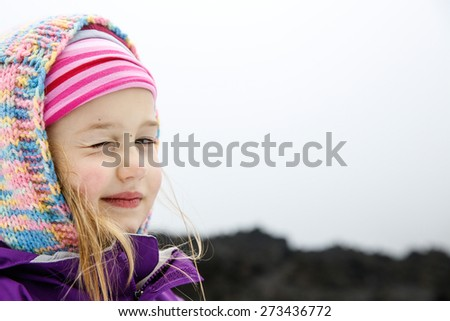 Portrait of playful and carefree, cute little Caucasian girl winking at mum and dad on a trip to Mt. Etna, Sicily, Italy. Active family lifestyle, traveling family concept.  - stock photo
