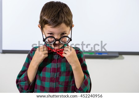 Portrait of playful boy holding bow while standing in classroom - stock photo