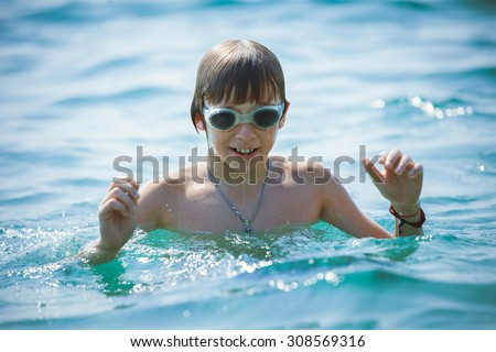 Portrait of playful boy in swimming goggles on sea - stock photo