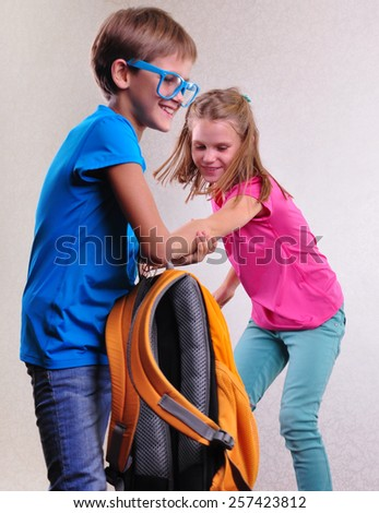 portrait of playful brother and sister with sunglasses fighting and having fun - stock photo