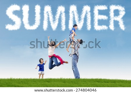 Portrait of playful family having fun together on the park with green grass under a summer's cloud - stock photo