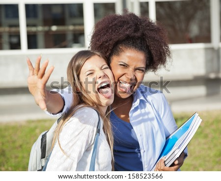 Portrait of playful female student with friend making facial expressions on university campus - stock photo