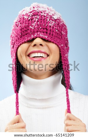 Portrait of playful woman in knitted winter cap smiling - stock photo