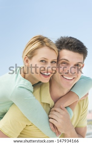 Portrait of playful young woman embracing man from behind against clear blue sky - stock photo
