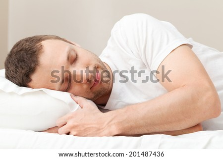 Portrait of pleased sleeping Young Caucasian man in white - stock photo
