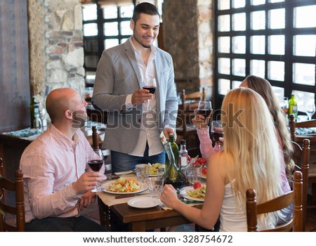 Portrait of positive adults having dinner in family restaurant. Focus on adult man - stock photo