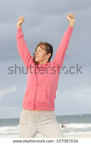 Portrait of positive and optimistic middle aged woman in winner pose outdoor at ocean, isolated with dark storm clouds and ocean as background and copy space. - stock photo