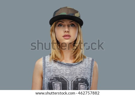 Portrait of positive blond female in baseball cap. Isolated on grey background.