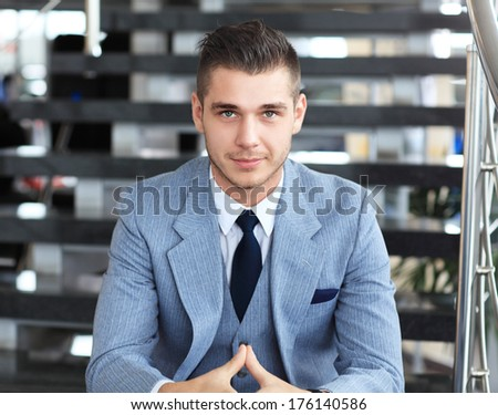 Portrait of positive business man sitting on stairs of modern office  - stock photo
