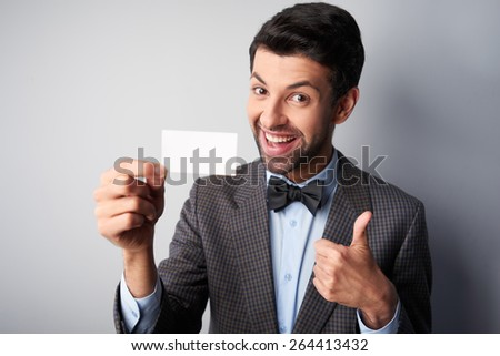 Portrait of positive casual young man wearing jacket and bow tie. Man smiling, showing thumb up and holding blank visiting card - stock photo