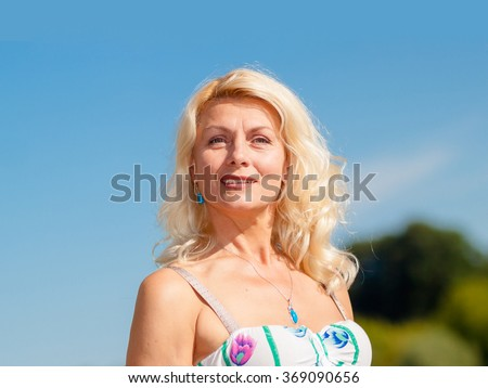Portrait of positive elderly blonde woman. Mature beautiful blonde in a white dress walks on the sandy road on blue sky background - stock photo