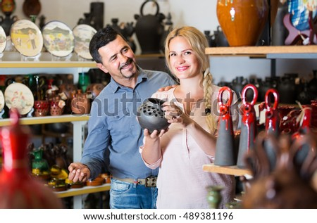portrait of positive european  man and woman shopping ceramic utensil in boutique