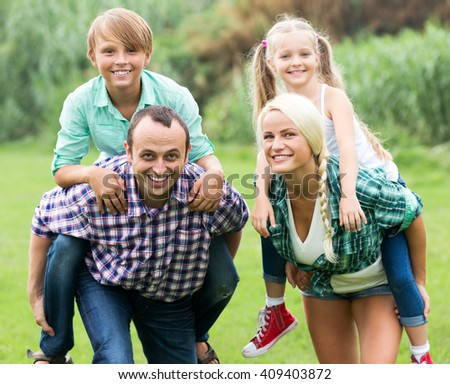 Portrait of positive family with children enjoying vacation in park