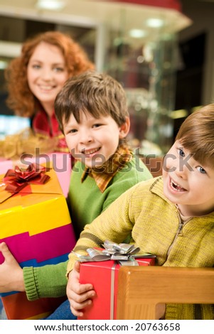 Portrait of positive lads holding gifts with their mommy at background