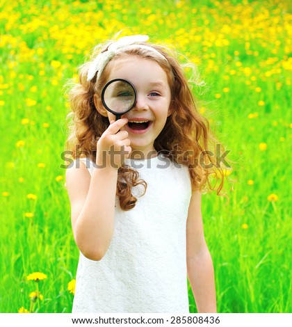 Portrait of positive little girl looking through a magnifying glass on summer floral field - stock photo
