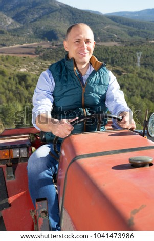 Portrait of positive man farmer sitting in tractor on background with large vineyard