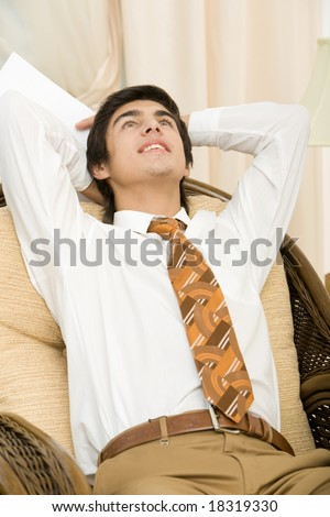 Portrait of positive man relaxing in arm-chair with hands behind head - stock photo