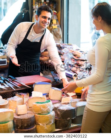 Portrait of positive seller offering different cheese and ordinary customer