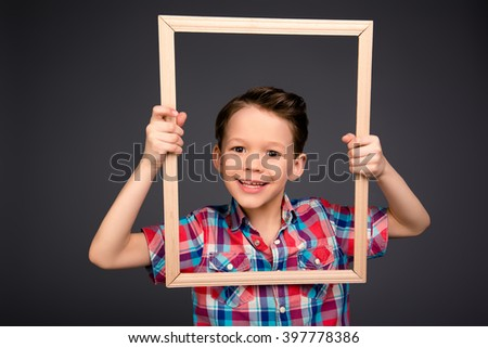 Portrait of positive smiling little boy holding frame - stock photo