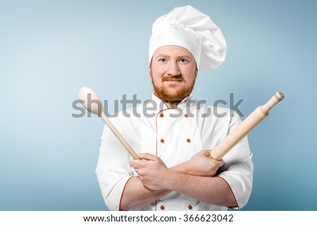 Portrait of positive young male chef in white uniform. Head-cook holding rolling-pin with big wooden spoon and standing against grey background - stock photo