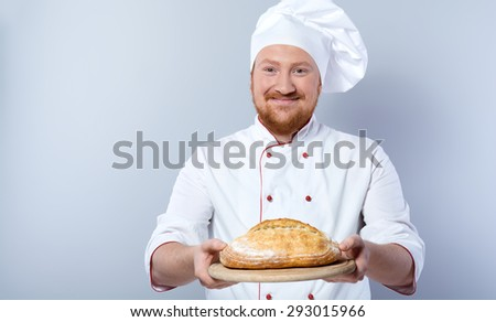 Portrait of positive young male chef in white uniform. Head-cook smiling, looking at camera and proposing freshly baked bread. Standing against grey background