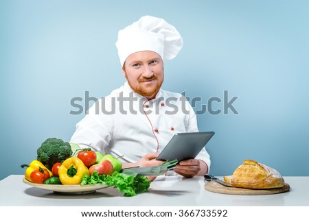 Portrait of positive young male chef in white uniform. Head-cook smiling, looking at camera and searching recipes by using tablet computer. Sitting against grey background near table with fresh food - stock photo