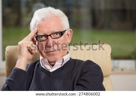Portrait of practiced profesional elderly psychologist - stock photo
