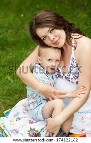 portrait of pregnant mother and her little son hugging in summer - stock photo