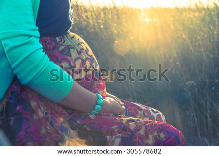 Portrait of pregnant woman bathing in sun rays - stock photo
