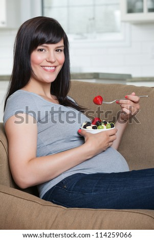 Portrait of pregnant woman eating fruit salad while sitting in sofa - stock photo