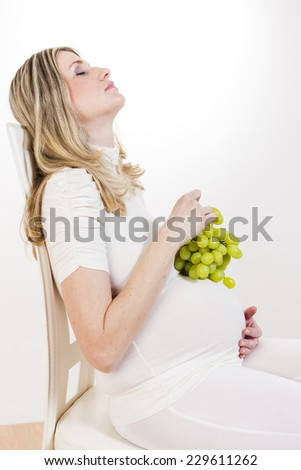 portrait of pregnant woman holding bunch of grape - stock photo