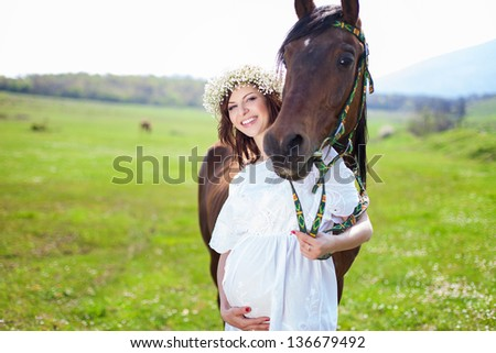 Portrait of pregnant woman in wreath near horse