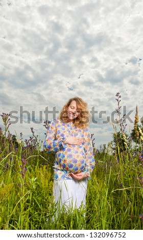 Portrait of pregnant woman on the field - stock photo