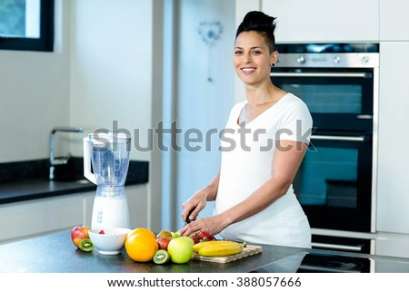 Portrait of pregnant woman smiling while cutting fruits on chopping board