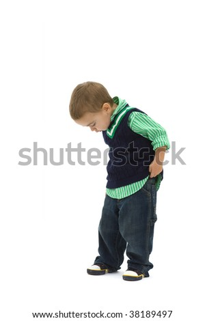 Portrait of preschoold boy posing green shirt and jeans, looking down, isolated on white.