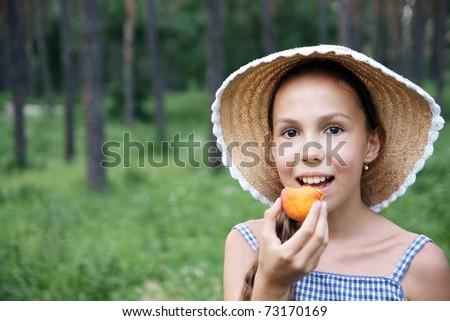 Portrait of preteen girl in straw hat eating apricot on green leaves background - stock photo