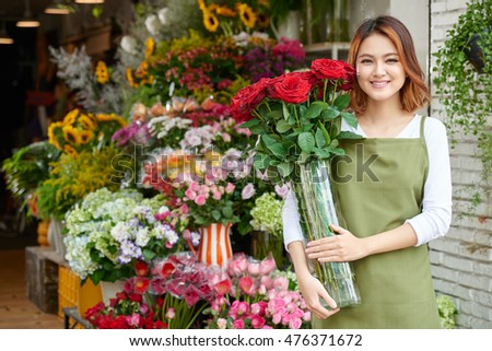 Portrait of pretty Asian florist with bouquet of roses