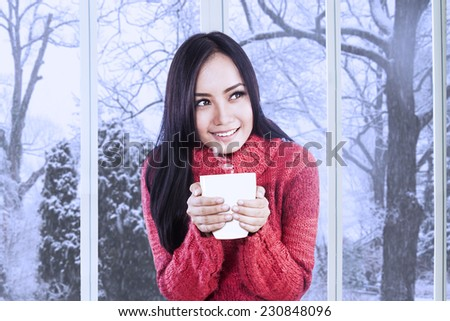 Portrait of pretty asian girl with a knitted clothes holding a cup of warm drink - stock photo