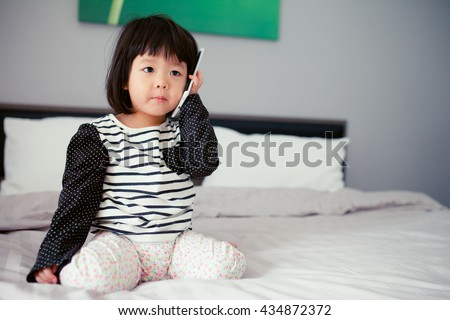 Portrait of pretty asian little girl talking on mobile phone on her bed. - stock photo