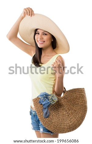 Portrait of pretty Asian young woman holding beach bag - stock photo