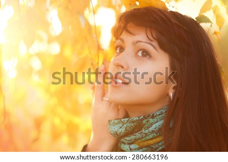 Portrait of pretty beautiful young girl in the evening sunshine in autumnal park in nature