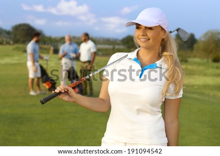 Portrait of pretty blonde female golfer with golf club, smiling, looking away. - stock photo