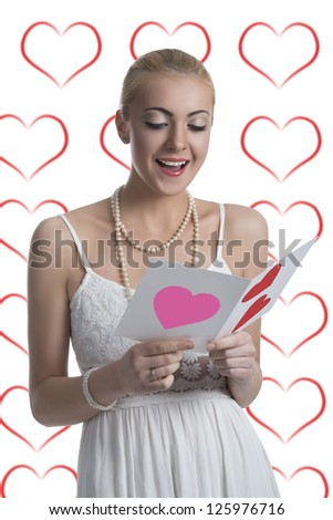 portrait of pretty blonde girl reading valentine postcard with happy expression and some heart on background - stock photo