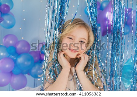 Portrait of Pretty blonde little girl with color balloons in a decorated studio - stock photo