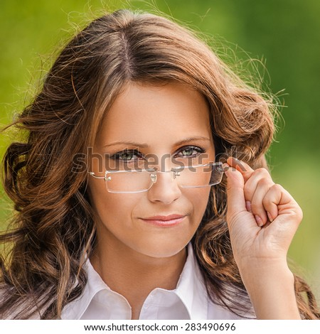 Portrait of pretty brunette young woman wearing eyeglasses and white blouse, standing at summer green park. - stock photo