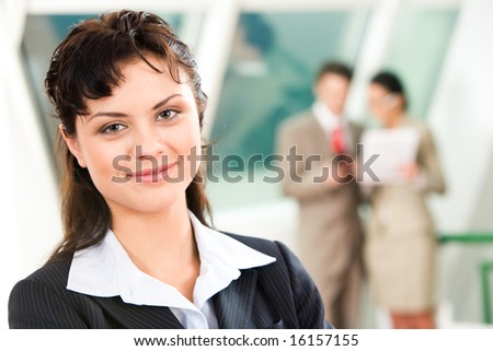 Portrait of pretty business leader in working environment looking at camera