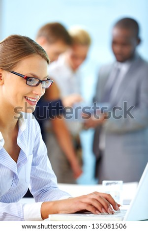 Portrait of pretty businesswoman typing on laptop at workplace - stock photo