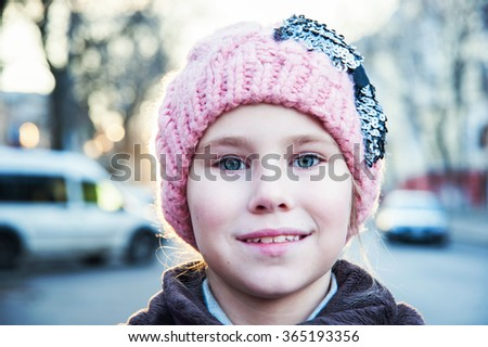 Portrait of pretty Caucasian girl standing in winter clothes and hat close up - stock photo