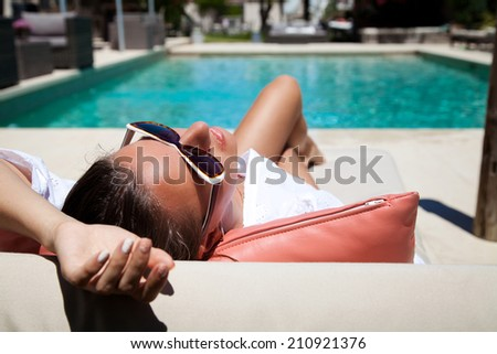 Portrait of pretty cheerful woman holding hand behind head, relaxing at the luxury poolside. Girl at travel spa resort pool. Summer luxury vacation. (focus on woman face)
