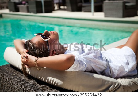 Portrait of pretty cheerful woman holding hand behind head, relaxing at the luxury poolside. Girl at travel spa resort pool. Summer luxury vacation. (focus on woman face) - stock photo
